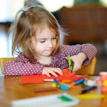 Little preschooler girl cutting colorful paper